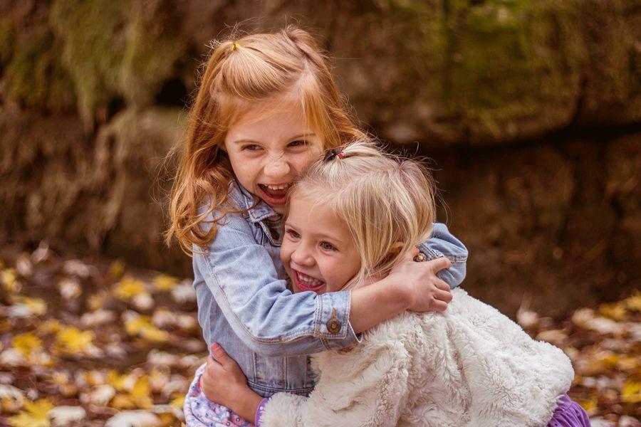 Zwei Mädchen umarmen sich und lachen.