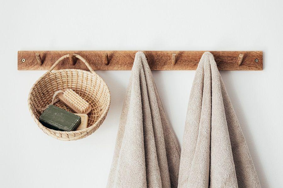 Holzbrett an der Wand, an dem zwei braune Handtücher hängen sowie ein Korb mit Seife und Bürste.