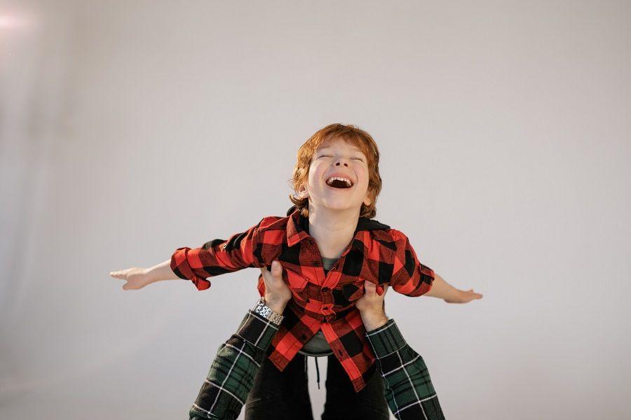 Junge wird auf Händen getragen und lacht.