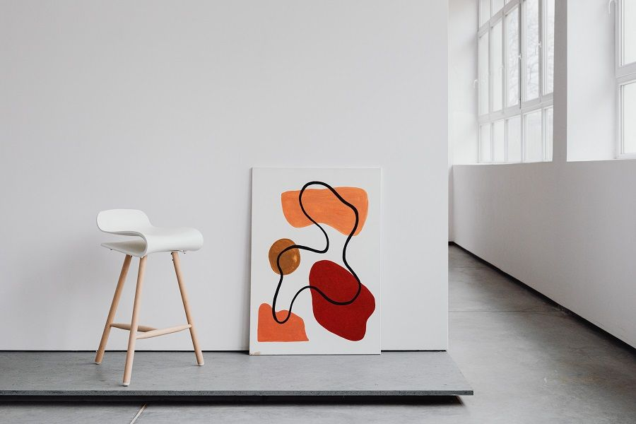 Heller Raum mit weißem Barhocker und minimalistischem Gemälde.