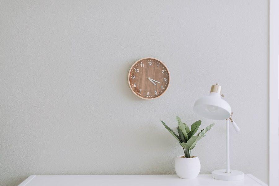 Schreibtisch mit Pflanze und Tischlampe, darüber eine Holzuhr an der weißen Wand.