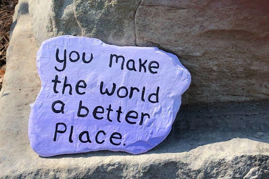 "Mit lila Farbe bemalter Stein mit der Aufschrift ""You make the world a better place."""