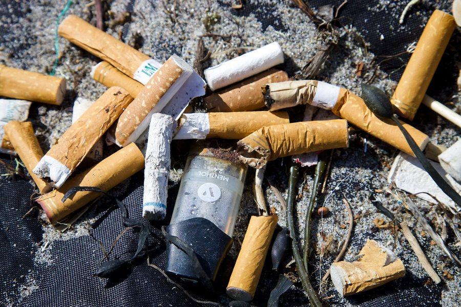 Zigarettenkippen und Plastikmüll am Strand